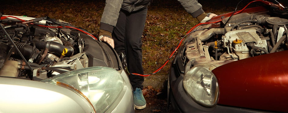guy charging a car battery with a jump starter cable