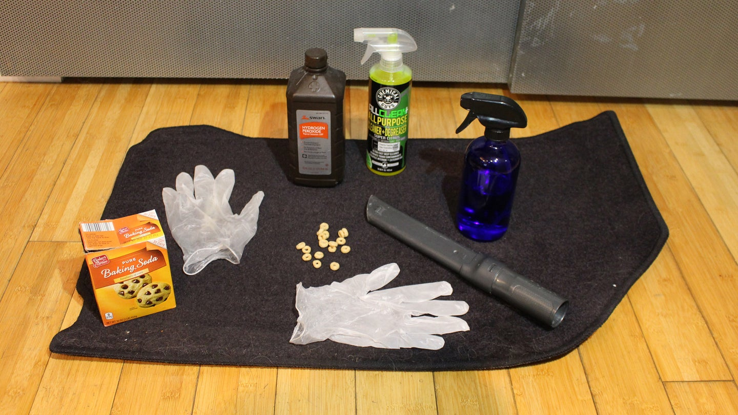 A set of gloves, hydrogen peroxide, baking soda, a spray bottle, and some interior car cleaner sit on top of a car floor mat.