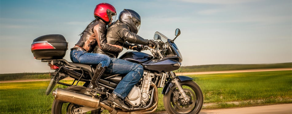 a couple riding a motorcycle