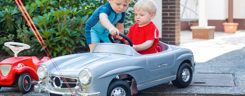 two boys playing with the electric car