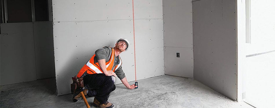 handyman measuring with a laser tool