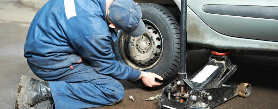 man trying to screw off the tire