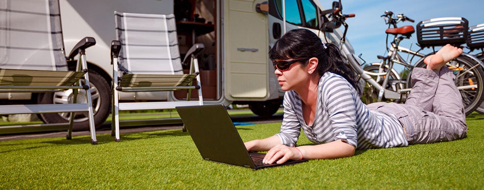 Woman looking at the laptop near RV