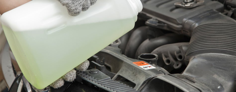pouring a coolant for car overheat