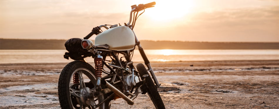 Retro motorcycle with sunset background