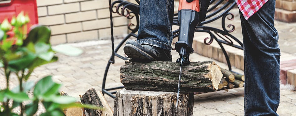 Man in plaid shirt sawing piece of wood on stump