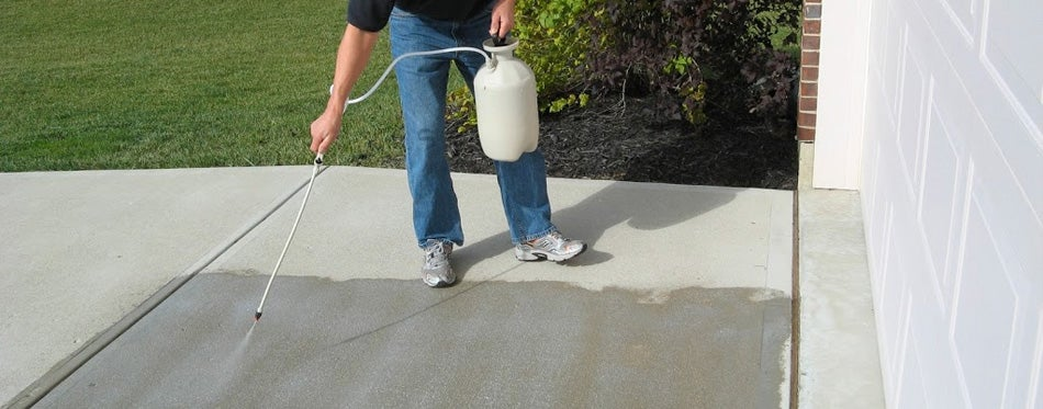 man applying concrete driveway sealer