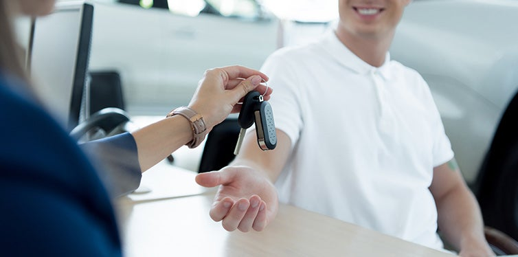 manager giving car key to customer