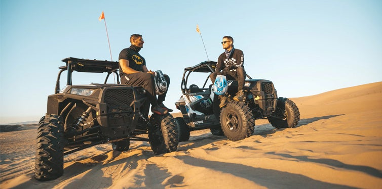 two men sitting on top of atv on desert