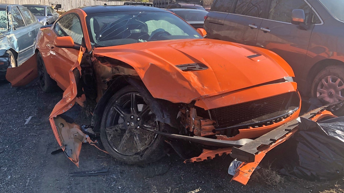 A wrecked orange Ford Mustang in a slavage yard.