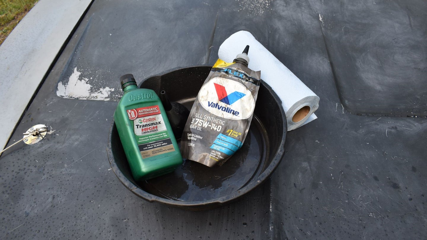 A catch pan with transmission fluid and shop towels.