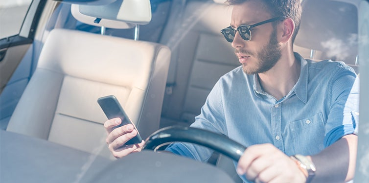 Man with smartphone driving car