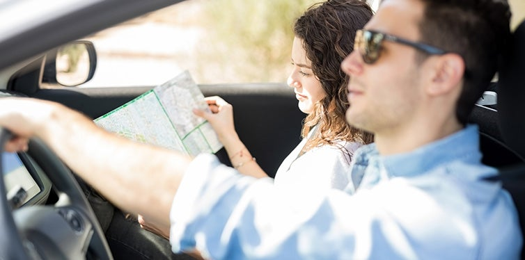 Young man driving car while his girlfriend looking in map