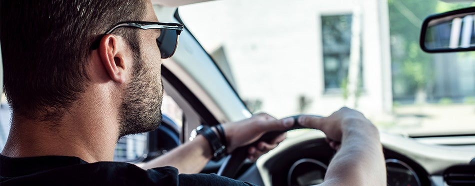 confident young man in sunglasses for driving
