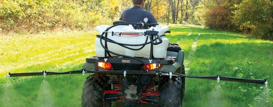 man riding atv with sprayer