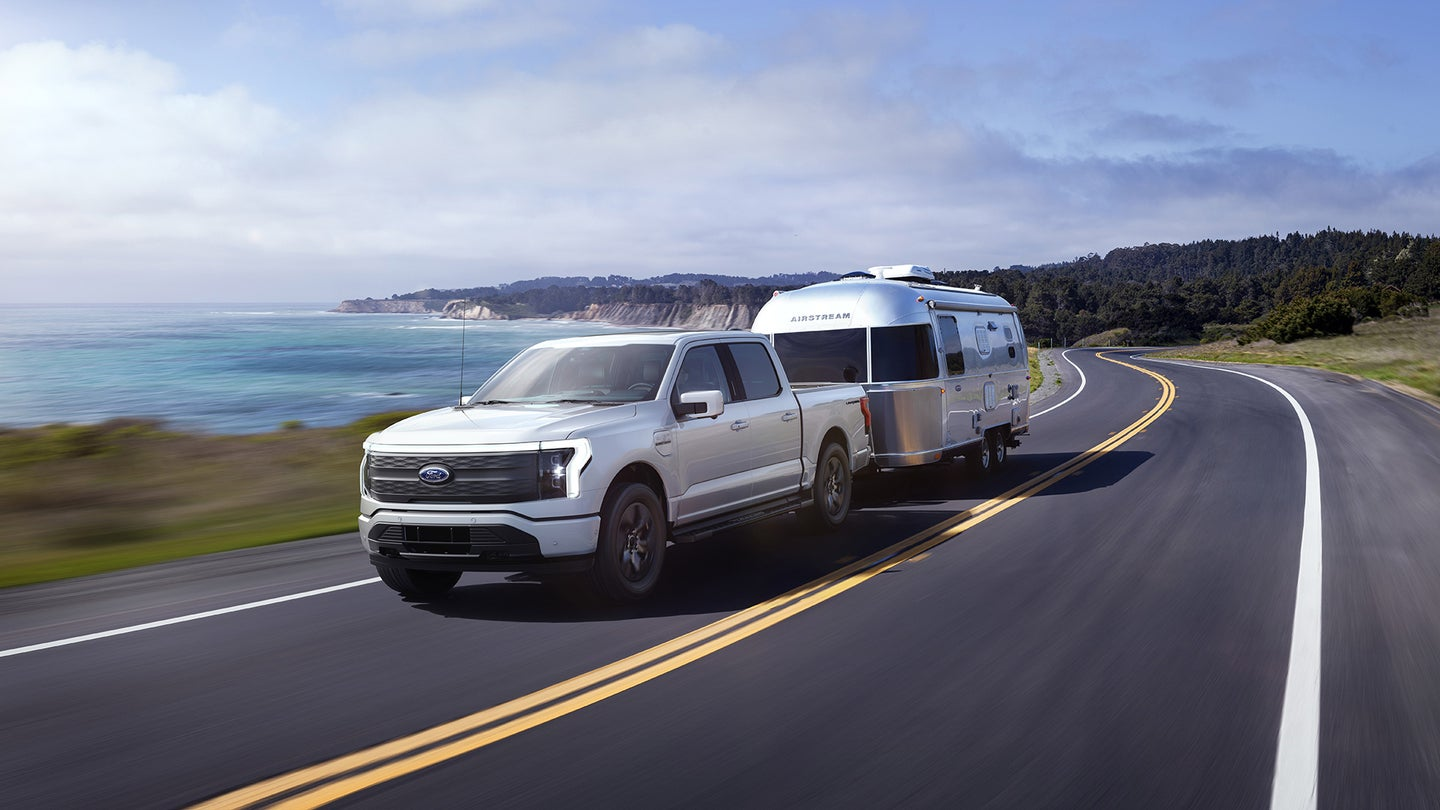 An electric Ford F-150 Lightning towing an Airstream down an oceanside road.