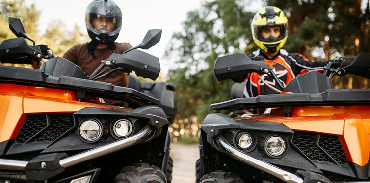 Two riders in helmets and equipment on quad bikes