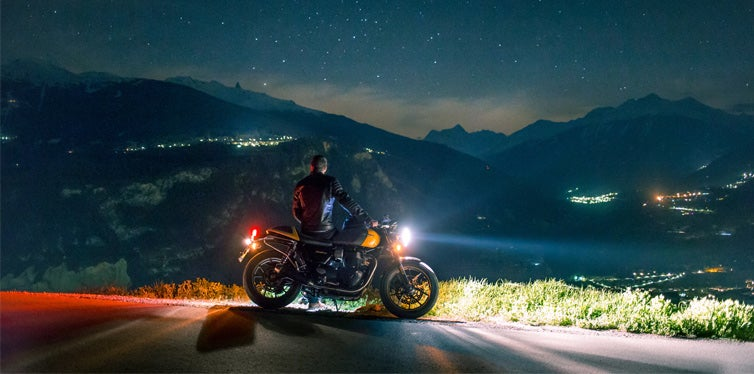 man siting on motorcycle at night
