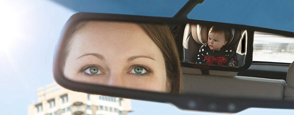 woman looking at car seat mirror