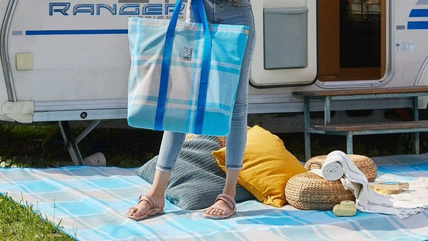 Woman holding a bag and standing on rv patio mats in front of an RV