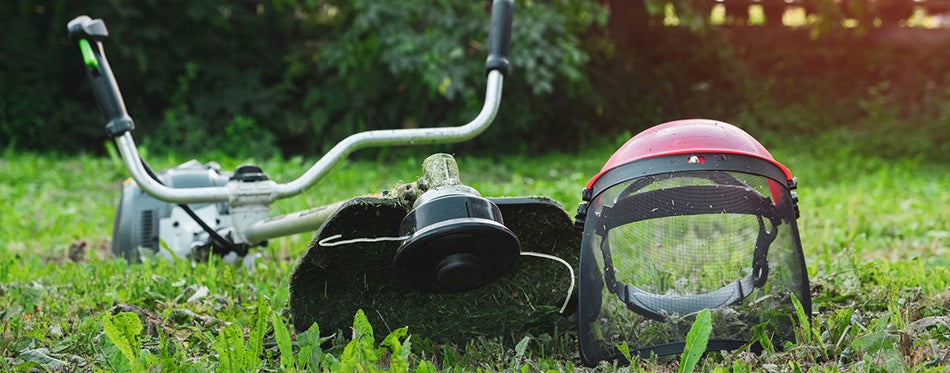 Grass trimmer on lawn in garden outdoors