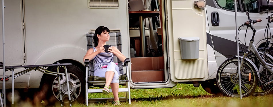 Woman is standing with a mug of coffee near the camper RV