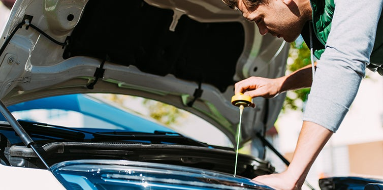 young man checking engine oil level