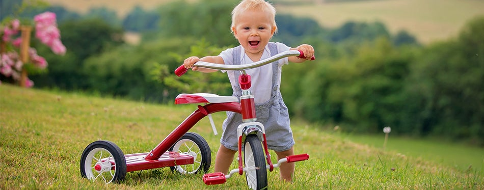 Cute toddler playing with tricycle