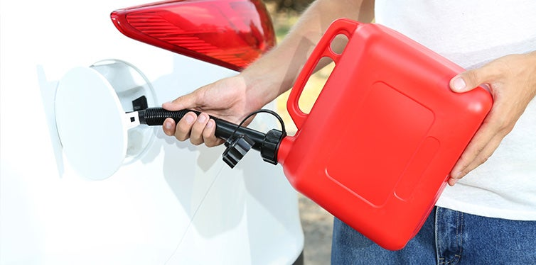 Man pouring fuel into gas tank of his car from red gas canister