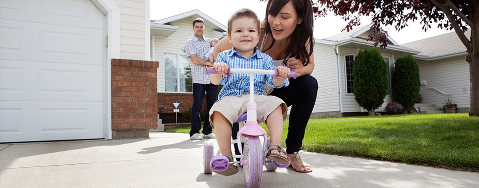 mother teaching son to ride bike