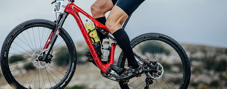 Closeup of athlete mountainbiker and sport bicycle