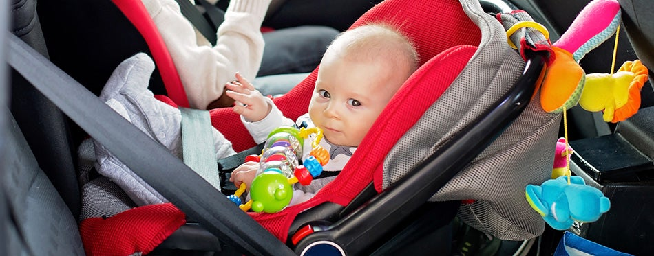 Little baby boy traveling in car seat with toys