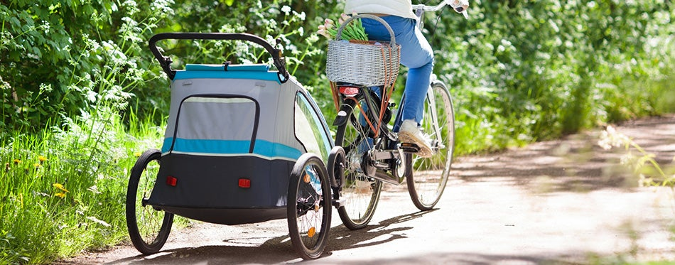 Mother on bicycle with baby bike trailer in park