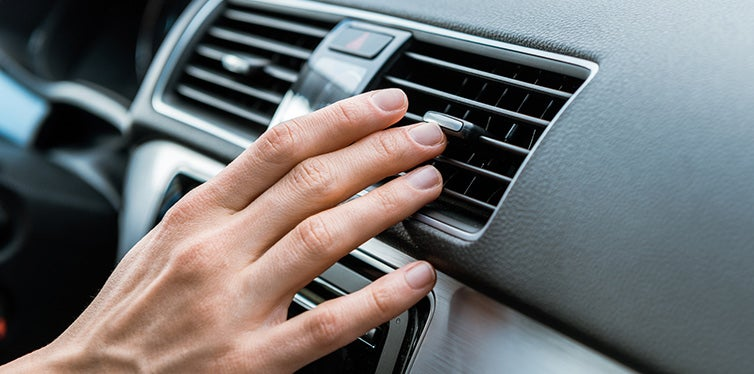 man touching air conditioner switch in car