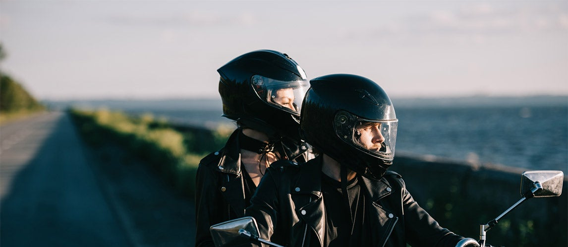 Two people riding motorcycle with cool motorcycle helmets