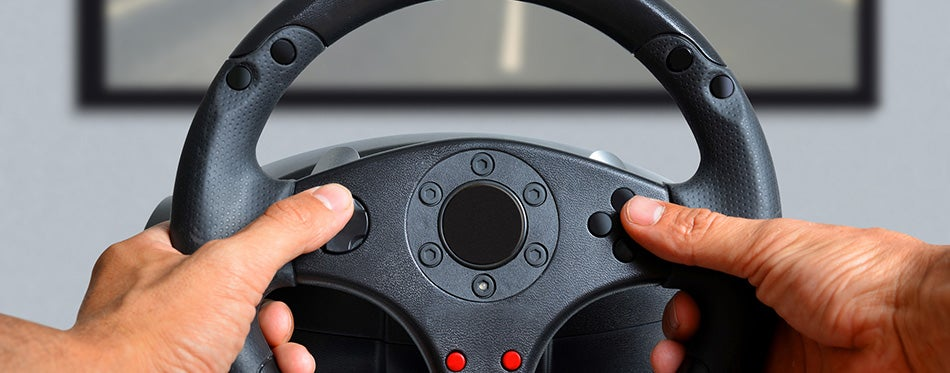 Hands holding gaming steering wheel