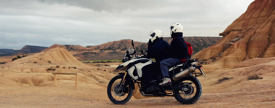 Tourists examining beautiful landscape wearing cool motorcycle helmets