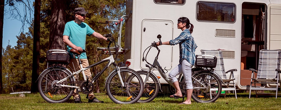 Woman with a man on electric bike resting at the campsite