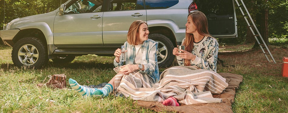 Women friends resting under blanket in campsite