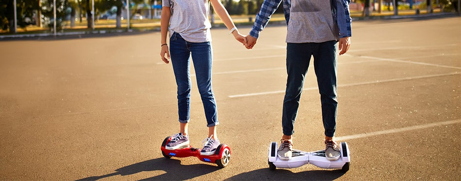 Young man and woman riding on the Hoverboard