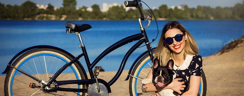 Beautiful young woman on the beach with bicycle
