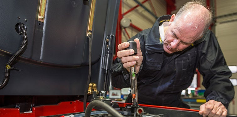 Mechanic checking car batery with hydrometer