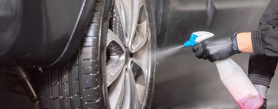 Professional car washer cleaning alloy wheels