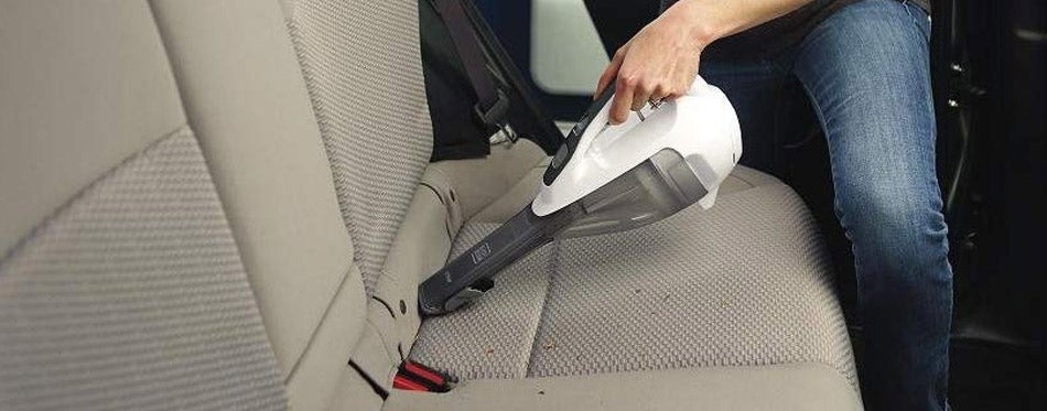 Woman cleaning seats with vacuum cleaner