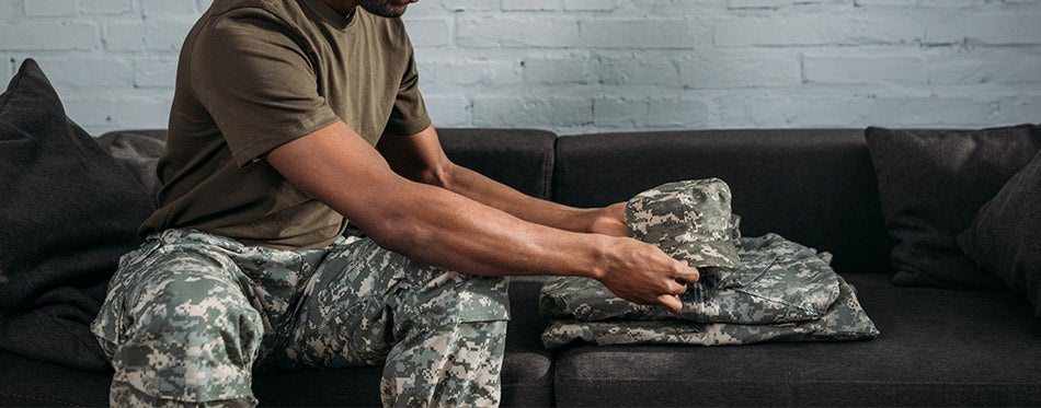 soldier folding camouflage clothes