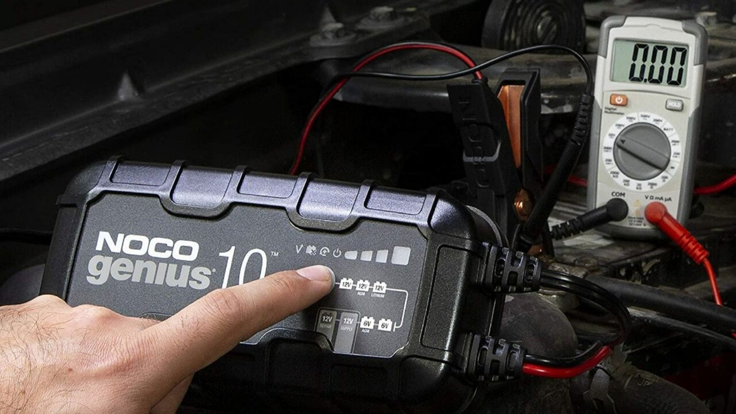 A man's hand points to battery maintainer