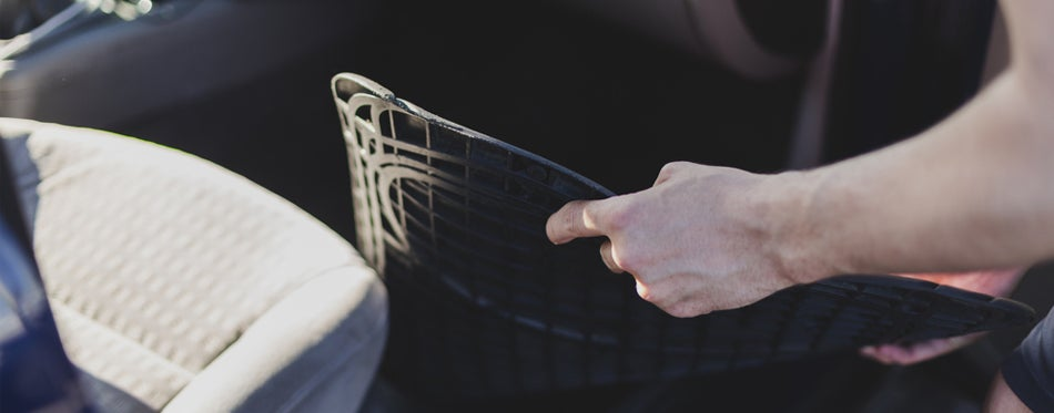 Man inserting all-weather floor mat into car