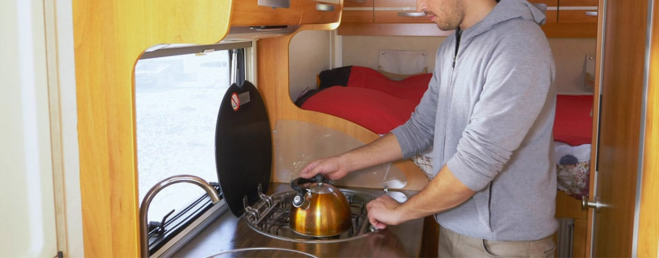 A man washes dishes in a motorhome