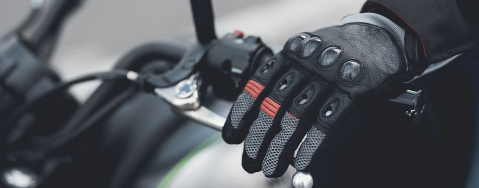 Biker holding the bicycle while wearing modern motorcycle racing gloves