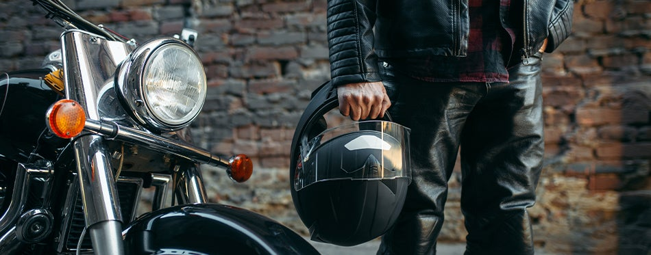 Man holding black motorcycle racing helmet near his motorcycle